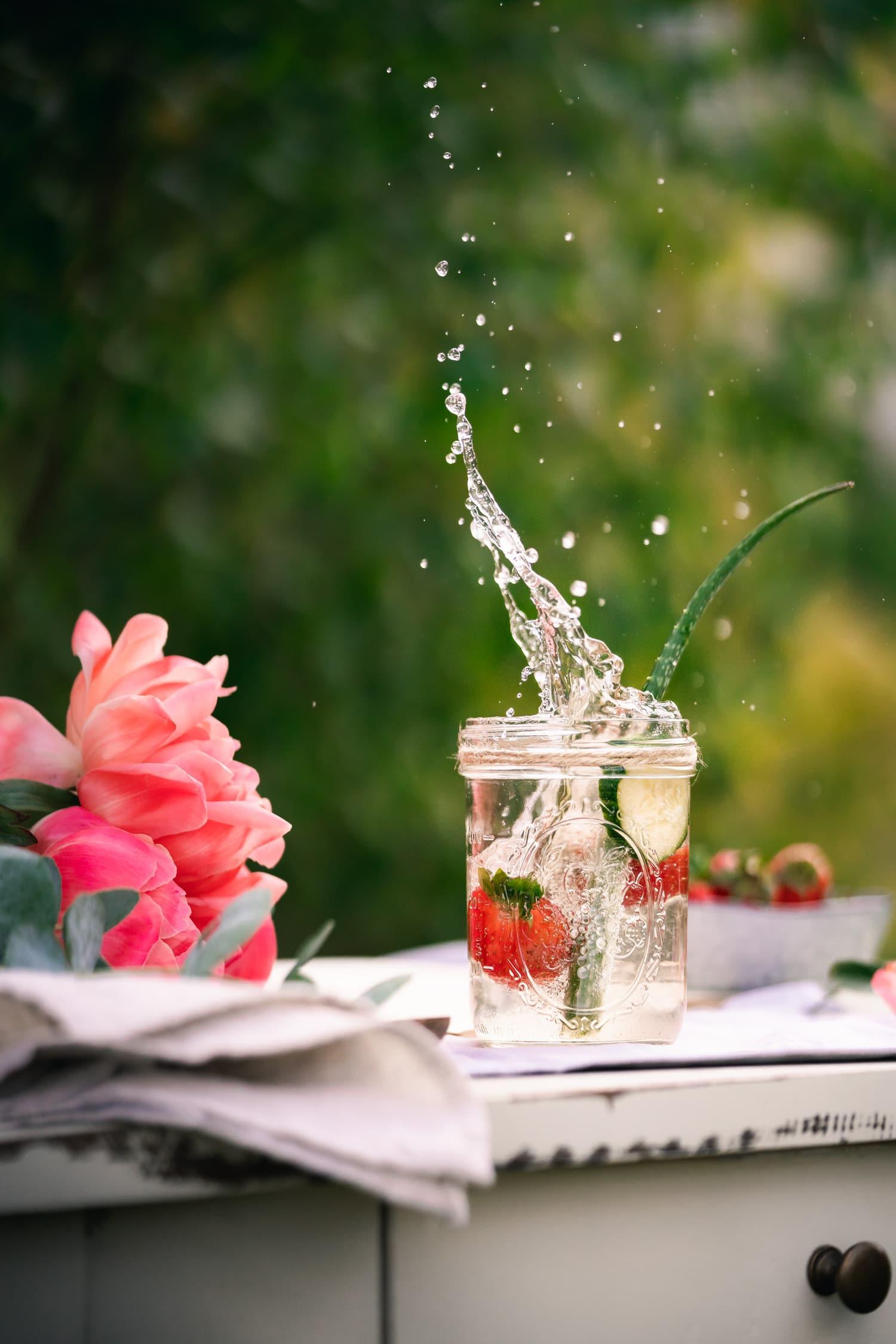 Wasser mit Geschmack :Erdbeere ins Glas gefallen mit Wasserspritzern