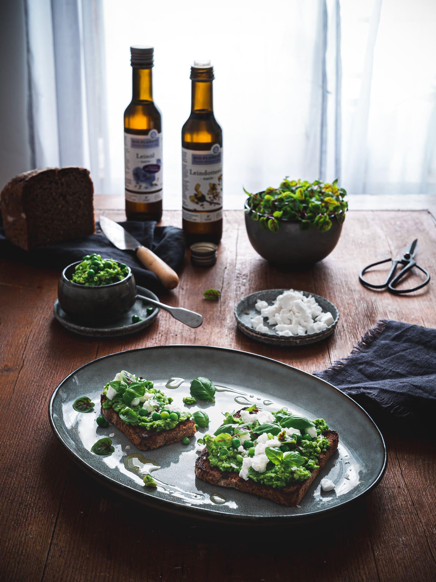Leindotteröl und Leinöl mit Erbsenpüree, gerösteten Brot, veganem Feta und Basilikum